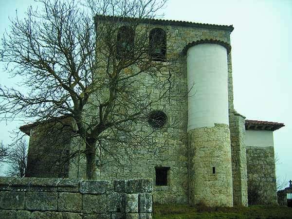 Imagen de la iglesia de San Román, en la que se aprecia la torre y el atrio exterior de piedra.